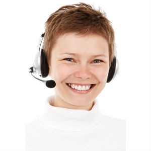 Woman smiling and wearing the type of headset worn at call center jobs.