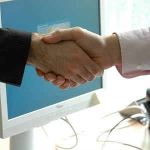 Two people shaking hands in front of a computer screen.