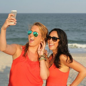 If you're not beach ready find out how the best exercise apps can help you get there. Two girls taking a selfie with their phone at the beach.