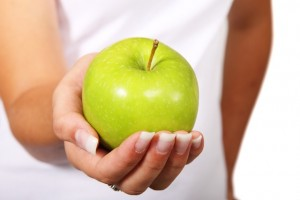 A woman holding a green apple. make a commitment to proper nutrition.