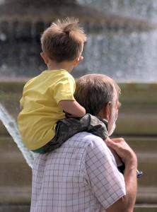 Grandfather holding his young grandson on his shoulders.