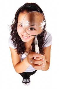 Improve you balance by getting your eyes checked. This image is of a girl looking through a magnifying glass.