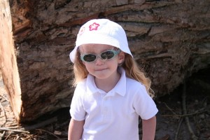 A little girl protected by the sun with a hat, sunglasses and light colored clothing.