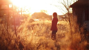 Girl standing in a field with sunlight shining on her.